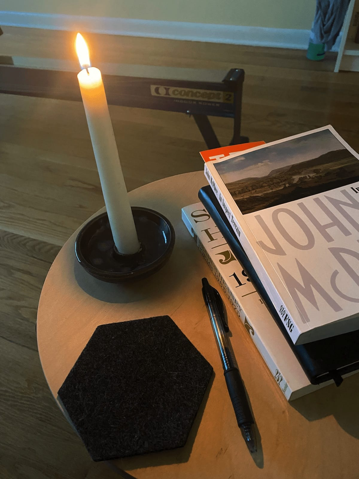 Taper candle with books and pen