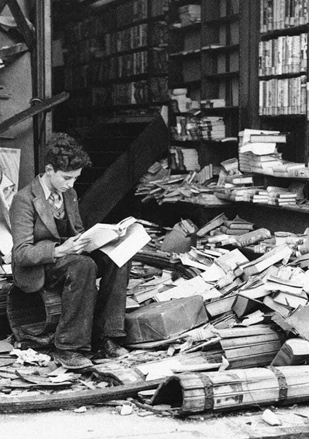 Boy reading in bombed bookstore. London, 1940.